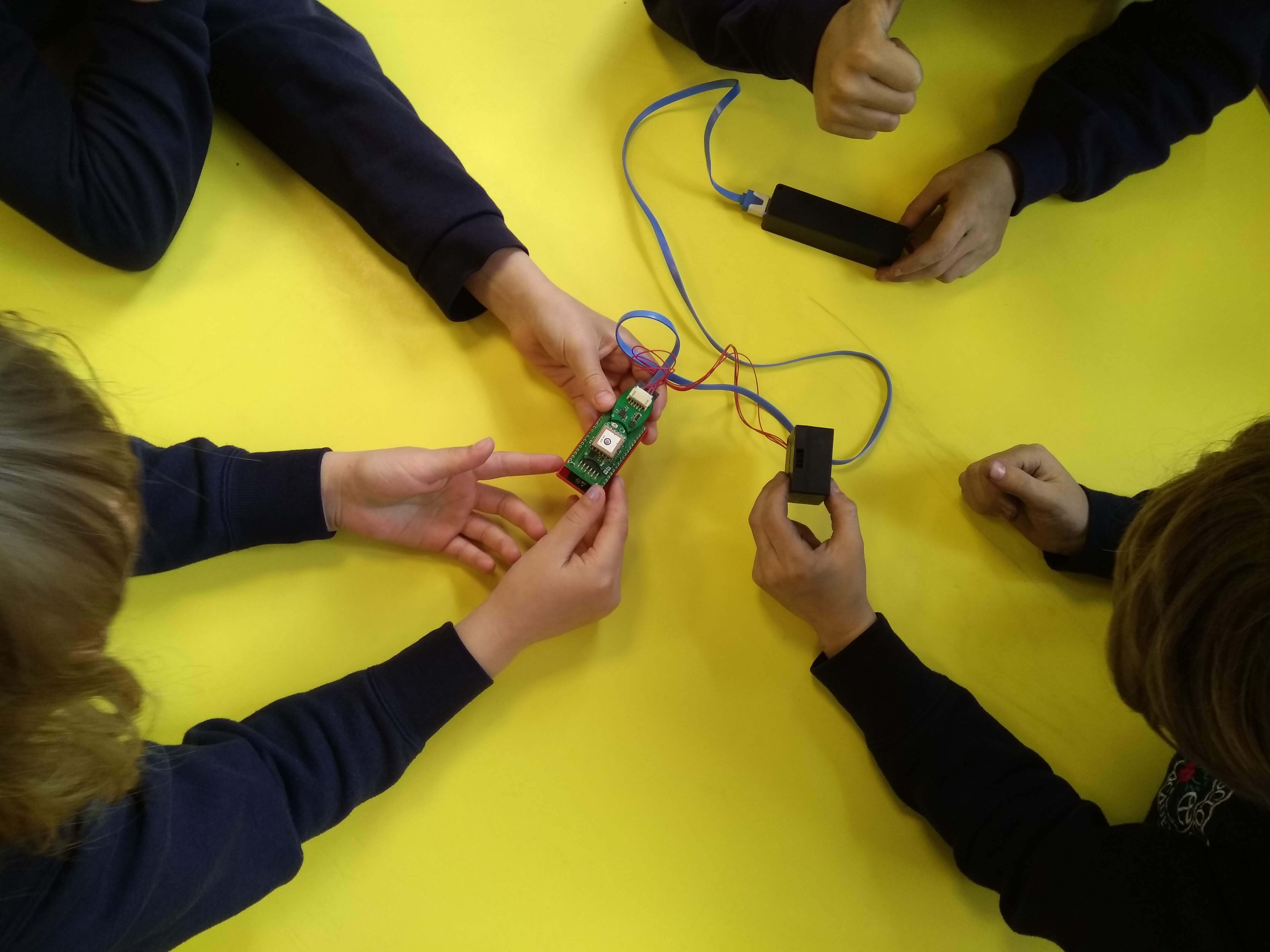 children collaborating around a table with air quality sensor project